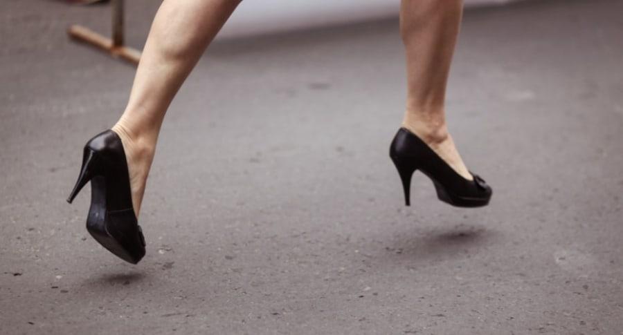 Mujer corre en tacones.