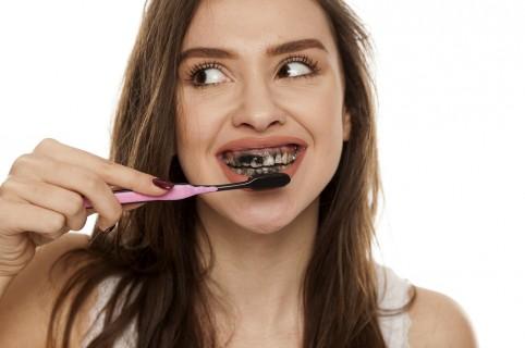 Lavando los dientes con crema de dientes de carbón