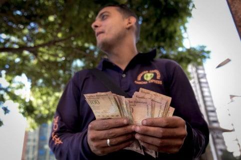 Hombre cuenta billetes de 100 bolívares