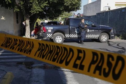 Policías municipales custodian una finca donde fueron halladas las víctimas.