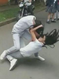 Estudiantes peleando a las afueras de su colegio, en Caicedonia