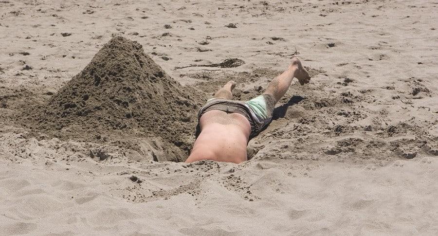 Hombre en hueco en una playa