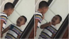 Niño se mira al espejo.
