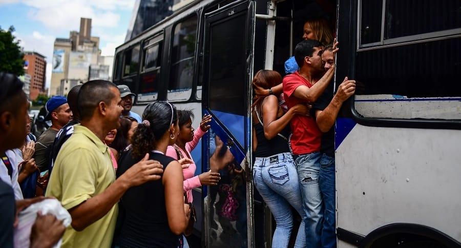 Personas subiendo a bus e Caracas
