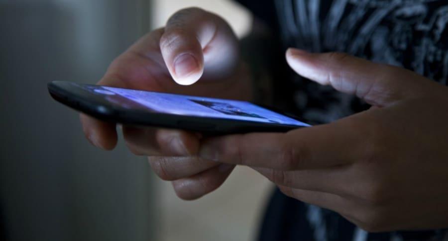 Mujer revisa celular.