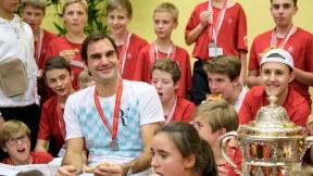 Roger Federer con recogebolas