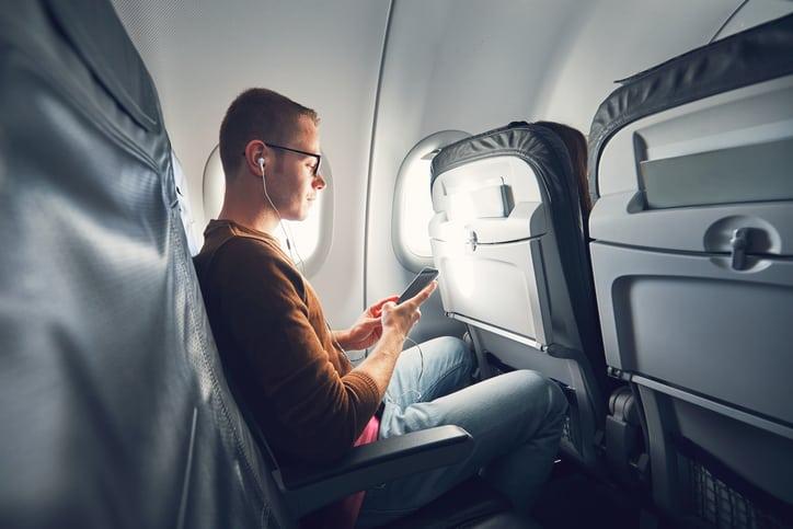 Hombre con celular en avión