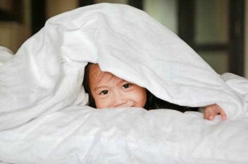 Niña escondida en la cama.