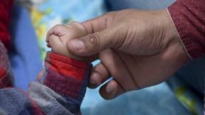 Hombre toma mano de bebé