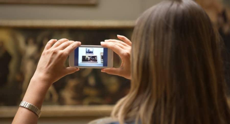 Mujer toma foto en museo.
