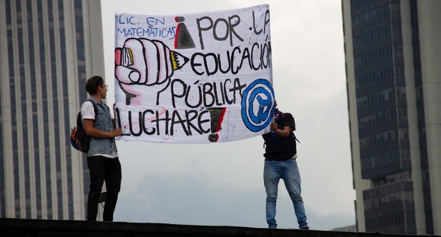 Dos jóvenes protestan por una mejor educación pública con una pancarta