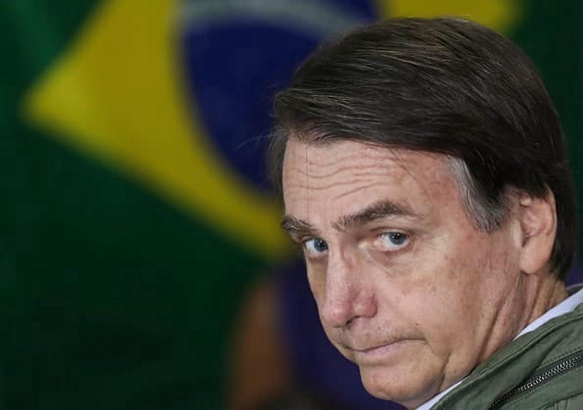 Presidente Bolsonaro con la bandera de Brasil de fondo