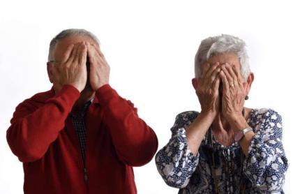Abuelos tapan sus caras.