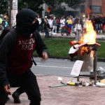 Dos formas de protesta: jóven encapuchado, frente a jóvenes con cartel