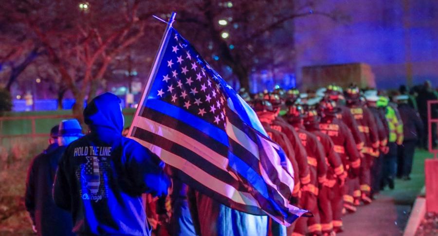 Bomberos y policías esperan el paso de una ambulancia del departamento de bomberos de Chicago
