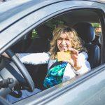 Mujer exhibiendo su licencia mientras conduce un automóvil