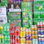 Botellas de gaseosa y cajas de cerveza apiladas en un comercio.