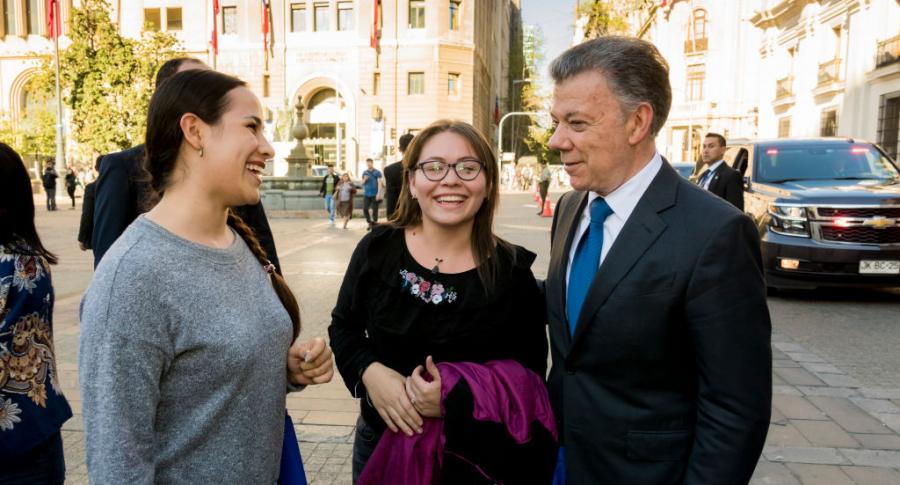 Juan Manuel Santos habla con turistas frente al Palacio de La Moneda, de Chile