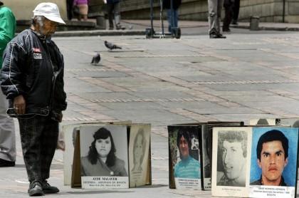 Hombre observando fotos de víctimas