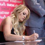 Stormy Daniels firma una foto en una sesión de autógrafos en Hollywood.