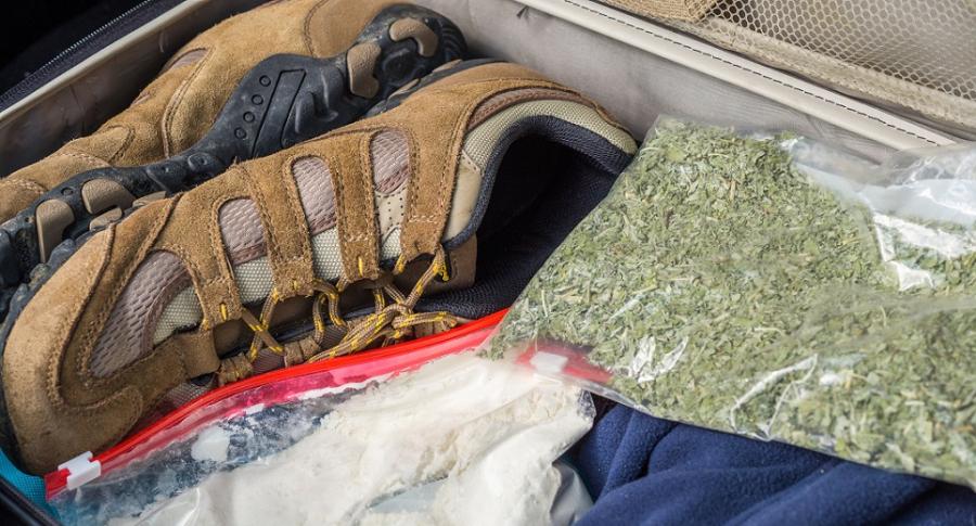 Ilustración de una maleta descubierta con drogas