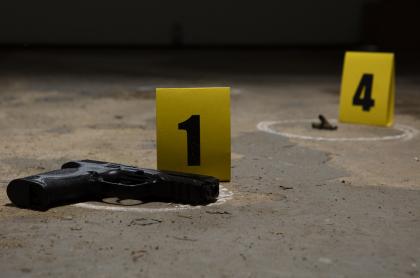 Una pistola y casquillos de bala, como pruebas de una investigación.