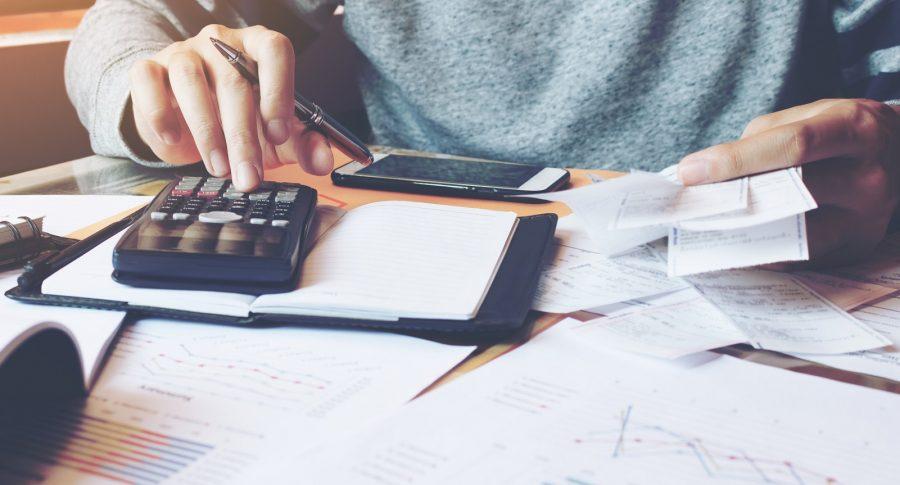 Hombre haciendo cálculos de sus gastos con sus facturas.