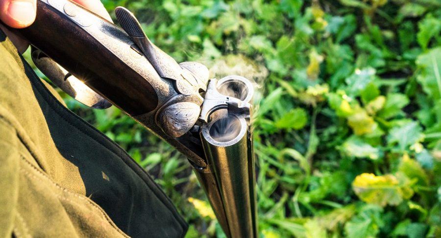 Primer plano de un hombre que sostiene una escopeta de 12 cañones.