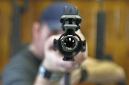 Hombre apuntando con arma larga