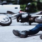Hombre caído junto a una motocicleta y una camioneta