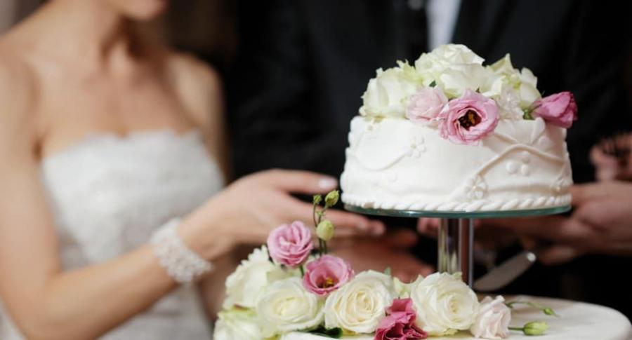 Novios parten pastel de boda.