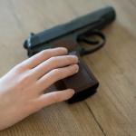 Nino agarrando una pistola, arma de fuego