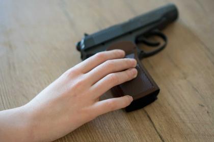 Nino agarrando una pistola de una mesa casera.
