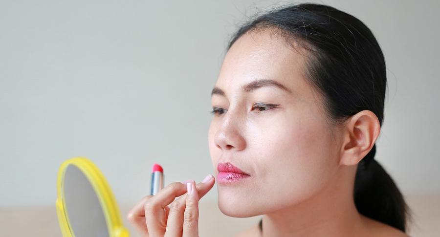 Mujer aplicándose labial