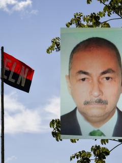 José Aldemar Rojas Rodríguez y una bandera del Eln