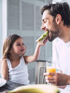 Niña dándole de comer a su papá