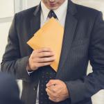Un hombre de negocios guarda un sobre en su saco