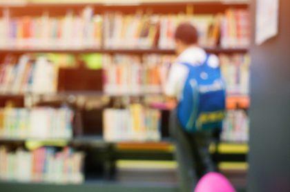 Niño en biblioteca, desenfocado