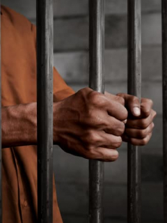 Manos de hombre agarrando barrotes de cárcel