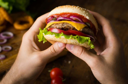 Hombre sostiene hamburguesa.