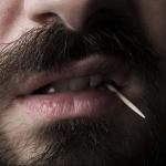Hombre con palillo en la boca.