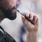 Hombre usa cigarrillo electrónico.