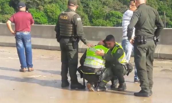 Policías abrazados y llorando porque mujer se lanzó desde puente con su hijo