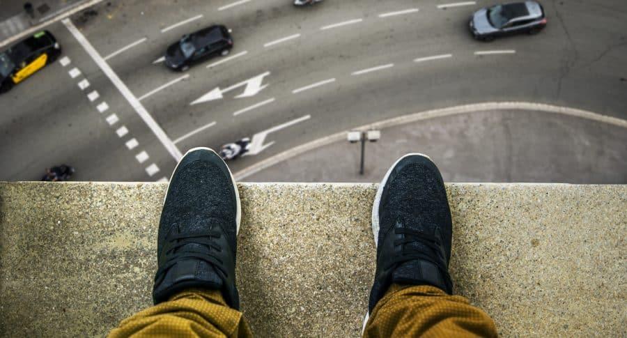 Pies de una persona parada al borde de un edificio alto