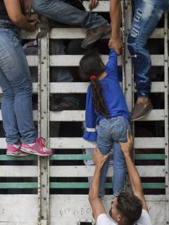 Venezolanos trepan a un camión en la vía Cucuta - Pamplona