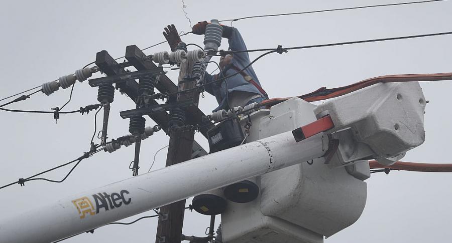 Un empleado trabaja en la restauración de una línea eléctrica