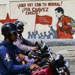 Motociclistas pasan frente a paredes pintadas con Chávez y Maduro