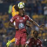 Enner Valencia (atrás) de Tigres disputa el balón con stiven Barreiro (adelante)