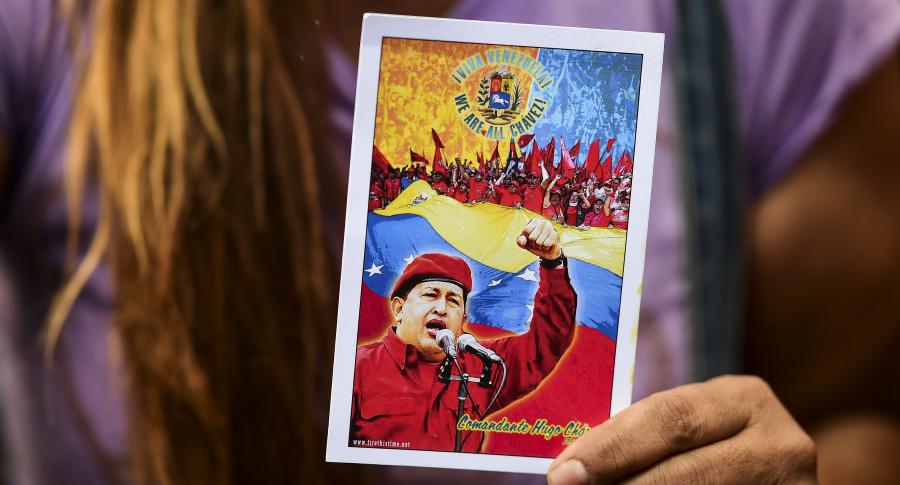 Una mujer sostiene una tarjeta con la imagen de Hugo Chávez