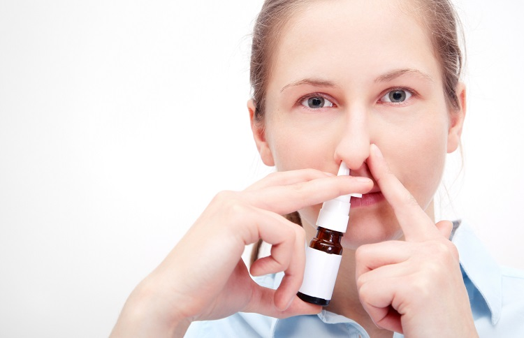 Mujer usando espray nasal